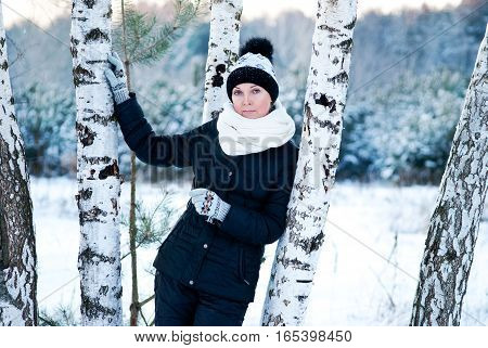 winter woman standing on the background of Russian birch in the snow