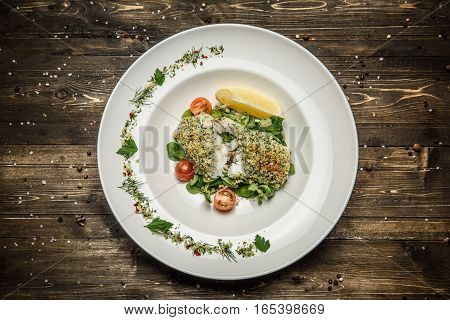 fish steak with herbs, lemon, cherry tomatoes and spices on a white plate wooden background.