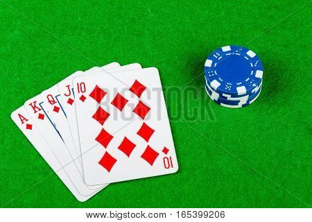 Royal flush poker hand with a stack of betting chips