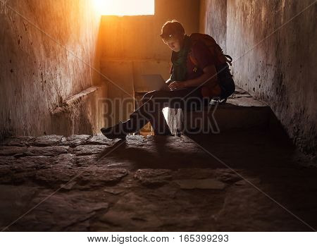 Tourist man surf internet with laptop in old tibet castle