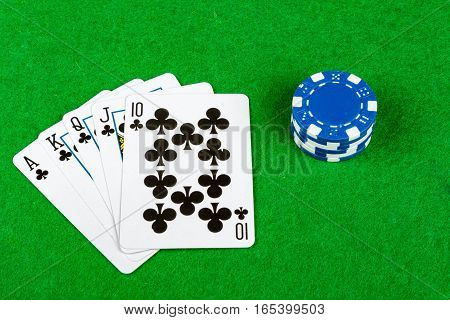 Royal flush poker hand with stack of betting chips