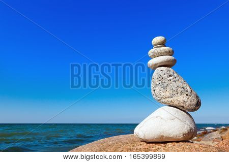 balance of white stones on a background of blue sky and sea