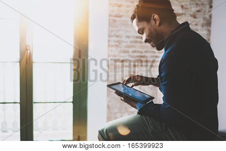 Smiling young African American freelancer touching screen digital tablet while working in new project at home. Black businessman looking for information on Internet. Blurred, color filter, flares.