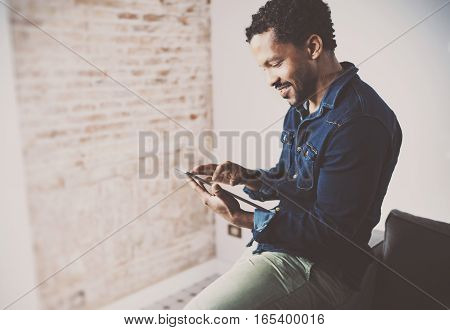 Smiling young African American freelancer touching display of digital tablet while working in new project at home. Black businessman looking for information on Internet. Blurred, color filter.