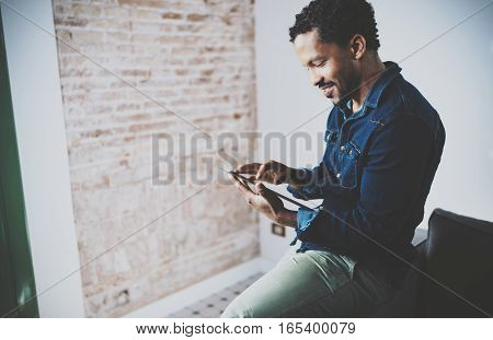 Musing young African American freelancer touching display of digital tablet while working in new project at home. Black businessman looking for information on Internet. Blurred, color filter.