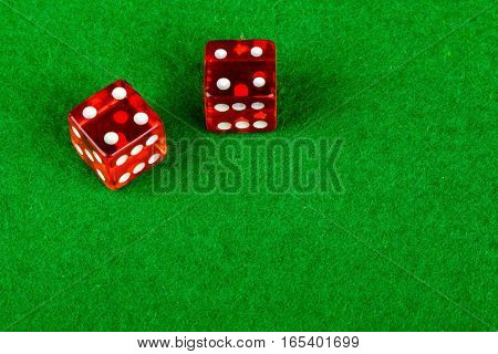 Gambling dice on a card table showing double 4