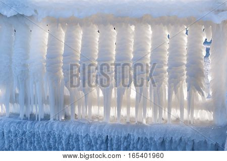 iced street fencing. Big long white icicles. Winter Ice Storm