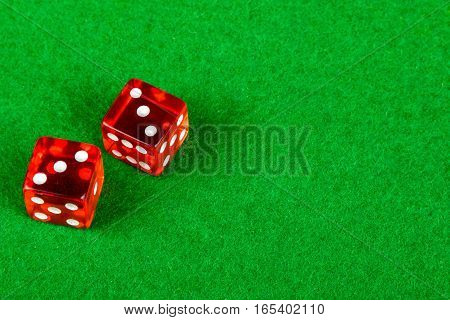 Gambling dice on a card table showing double 3