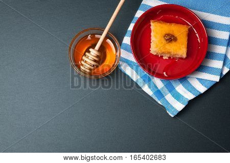 Small glass bowl of natural honey with wooden stick and sweet cake. On the black stone rustic table.
