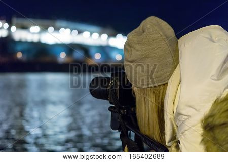 Young girl taking night view photos using DSLR and tripod on urban river bank. Girl night photography.