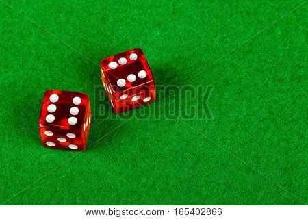 Two gambling dice on a card table showing double 6