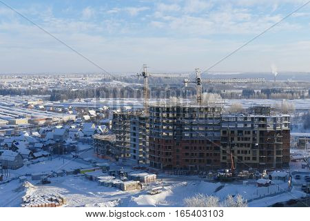 Large apartment buildings construction in new district among rural houses, urbanisation in action. Winter season