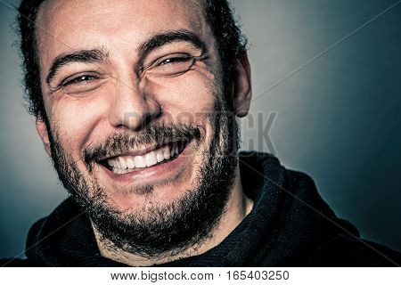 Joy and happiness, joyful and happy. A young man with beard smiling. Beautiful smile, blue eyes. Contentment and success concept.