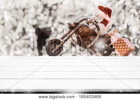 Empty Tabletop With Blurry Santa Bear Doll Ride A Bike With Christmas Gift Box Background For Montag
