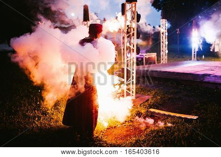Girl completely in smoke. In night wedding