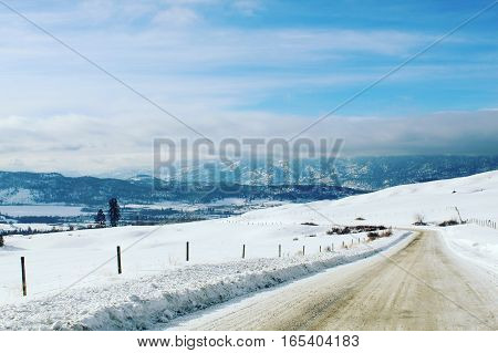Rural winter landscape with country road through snow covered hills. Mountains with clouds and blue sky background.