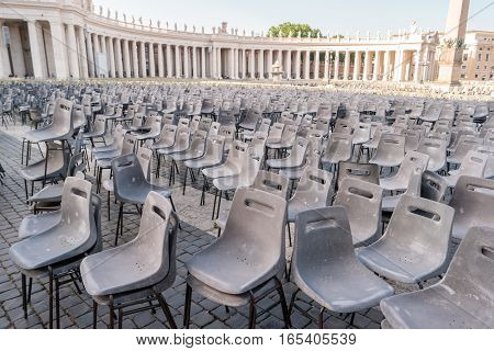 Many chairs outdoors. Columns and statues. Relax and admire the architecture.