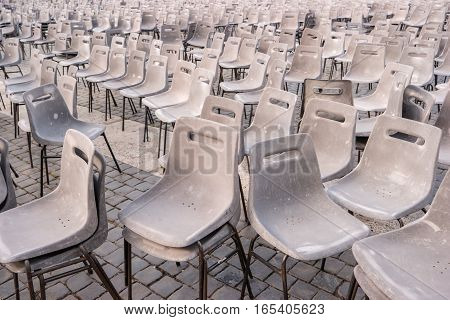 Gray chairs on pavement. Rows of plastic chairs. Take your seat.