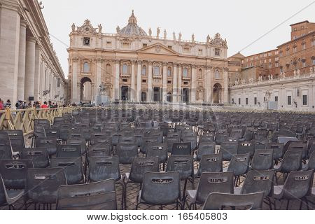 Building with statues and dome. Rows of chairs outdoor. Admire the masterpiece of architecture.