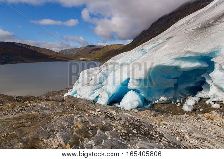 Ice front of Svartisen Glacier in Norway with lake and blue sky