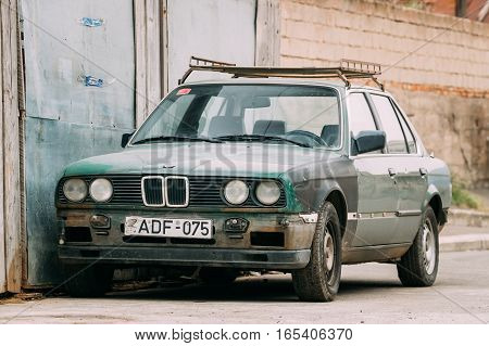 Tbilisi, Georgia - October 21, 2016: Old rusty sedan car BMW 3 Series, E30, parking on street. The BMW E30 is an entry-level luxury car which was produced by BMW from 1982 to 1994.