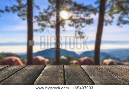 Wooden board empty table in front of tree background. Perspective brown wood over tent and pine tree can be used for display or montage your products. spring season. vintage filtered image.