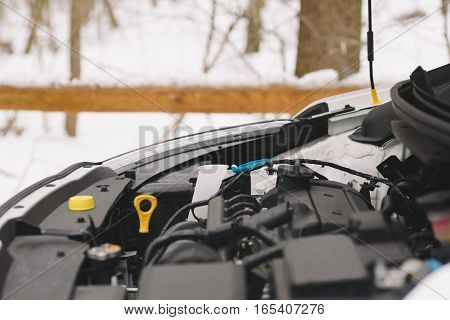Car engine closeup with copy space. Outdoor photo showing concept winter car problems with ignition.