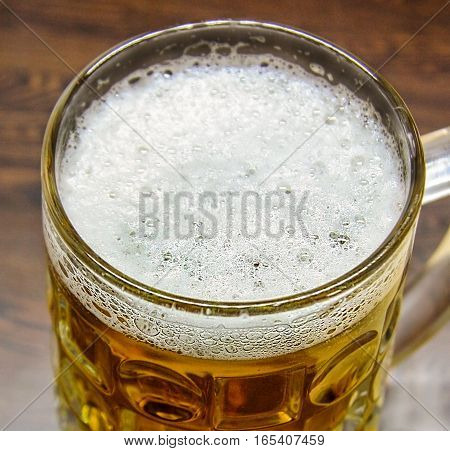 Big glass full of wheat beer on a textured wooden table