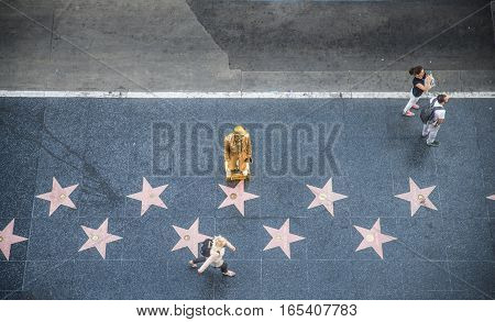 HOLLYWOOD CA - OCTOBER 12 2016: People visit Walk of Fame in Hollywood. Hollywood Walk of Fame features more than 2500 stars with inscribed celebrity names.