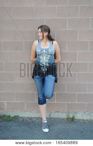 Female tomboy beauty expressions against a wall outdoors.