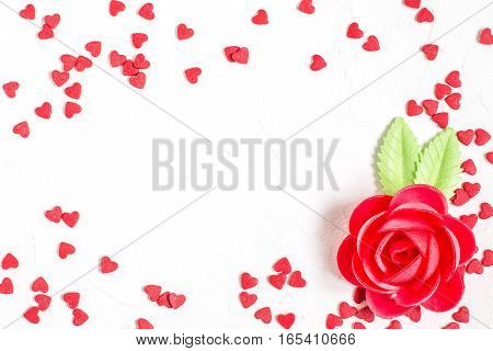 Frame sweet decorations: rose waffle and sugar hearts on a white textured background with space for text. The mood of tenderness and love. Symbols of Valentines Day