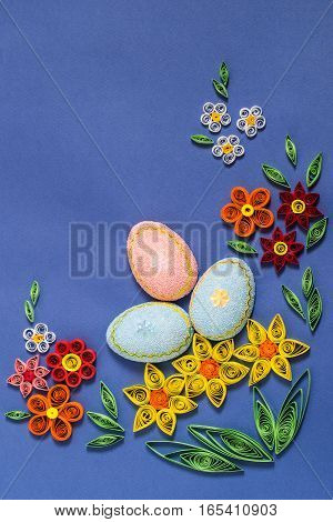 Colorful Easter composition with eggs and flowers in the technique of quilling on a blue background. Homemade application on paper. DIY Easter concept. Top view vertical