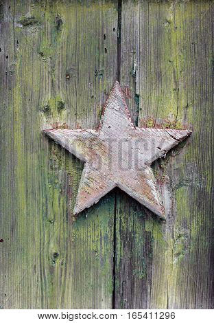 old wooden five-pointed star painted with peeling red paint on green wooden wall