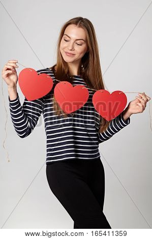 Beautiful smiling woman holding garland of three red paper hearts shape - blank copy space for letters or text, looking down at hearts