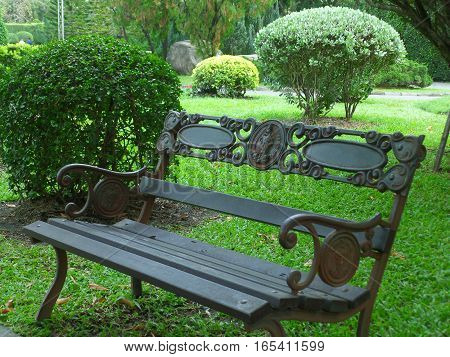 Have some rest!! Dark colored iron bench on the green grass field of public park