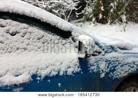 rear view mirror and side of car covered in snow