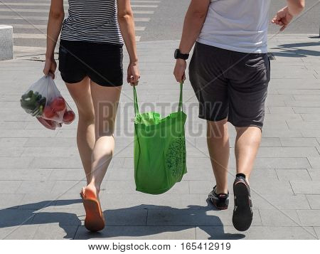 Bucharest Romania July 24 2016: A couple carrying shopping bags with food on the street in Bucharest.