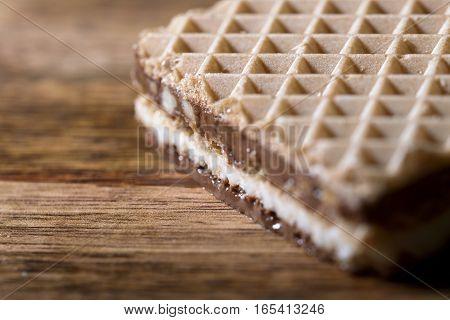 macro wafer stuffed with chocolate cream on wood