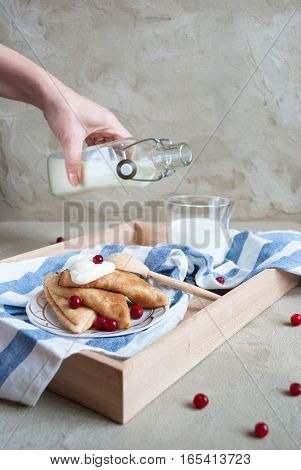 beautiful russian pancakes with sour cream, cranberry and bottle of fresh milk on concrete background