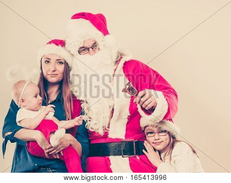 Christmas family concept. Mother toddler girl baby and man wearing Santa Claus costume.