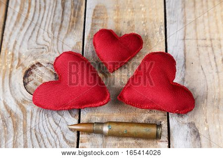 Three red heart made by hand next to a bullet on an old wooden table