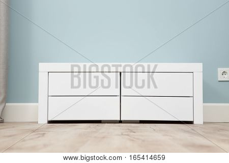 White colored cupboard represented on floor in house or hotel. White wardrobe with four shelves in bedroom.