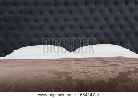 Buttoned texture of dark grey color. Closeup of white pillows represented on bed in bedroom or hotel room.