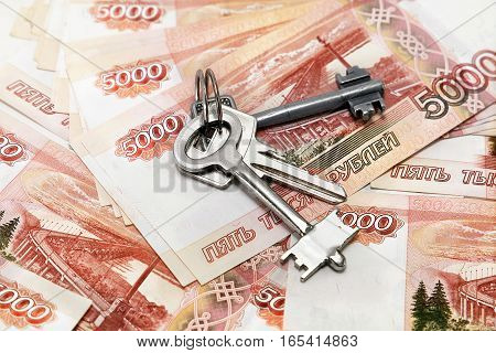 Bunch of keys on the background of Russian money. Buying a home