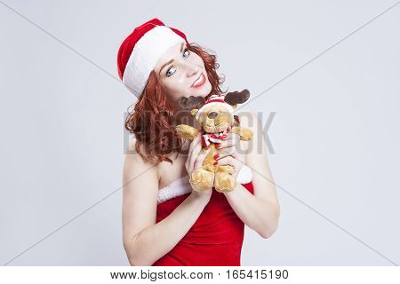 Portrait of Caucasian Santa Helper with Christmas Present in Hands. Over White Background. Horizontal Image Orientation