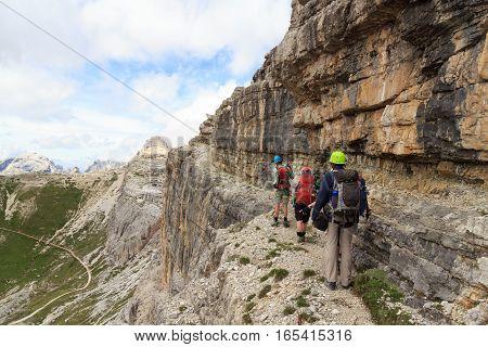 People hiking on via ferrata Alpinisteig in Sexten Dolomites mountains South Tyrol Italy