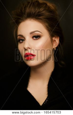 Portrait of beautiful woman with red lips in studio