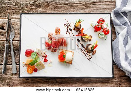 Appetizers for wine with cutlery flat lay. Top view on plate with delicatessen mix. Luxury lifestyle, expensive food, restaurant menu, gourmet concept