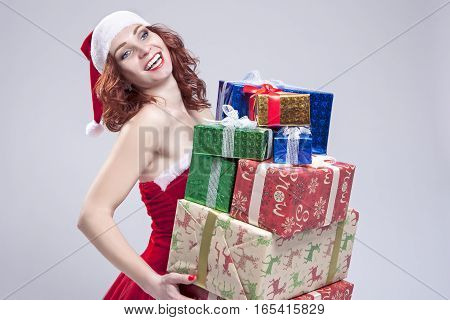Christmas and New Year Concept and Ideas. Positive Caucasian Snow Maiden Holding a Big Stack of Gift Boxes on Hands and Smiling. Posing on White. Horizontal Image Orientation