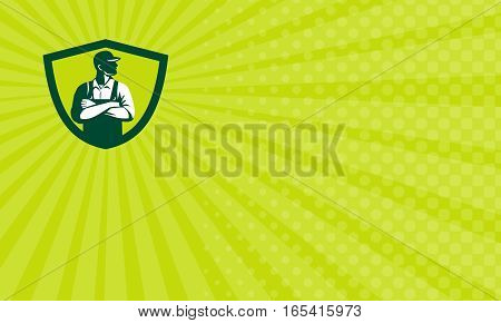 Business card showing Illustration of an organic farmer wearing hat and overalls arms folded looking to the side viewed from front set inside shield crest done in retro style.